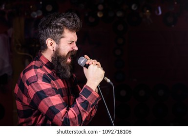 Man with tense face holds microphone, singing song, black background, copy space. Musician with beard and mustache singing song in karaoke. Soloist concept. Guy likes to sing in aggressive manner