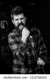 Man with tense face holds microphone, singing song, black background. Musician with beard and mustache singing song in karaoke. Vocalist concept. Guy likes to sing in aggressive manner.