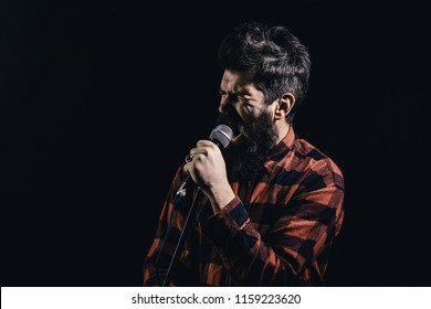 Man with tense face holds microphone, singing song, black background. Musician with beard and mustache lighted by spotlight. Talent show concept. Musician, singer makes effort to win musical contest.