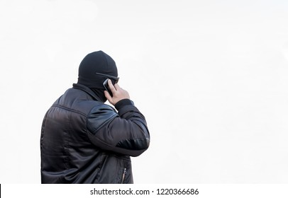 a man, a terrorist, a bandit in a black leather jacket and a mask talking on the phone