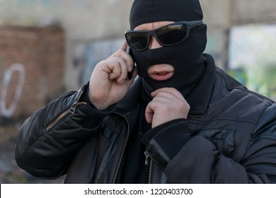 a man, a terrorist, a bandit in a black leather jacket and a mask talking on the phone on the street near an abandoned building