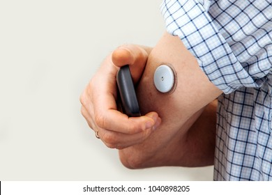 Man testing glucose level with a digital glucometer, sensor checkup glucose levels without blood. Diabetes treatment.