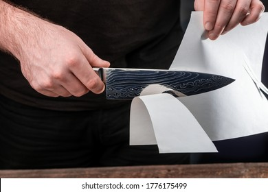 Man testing sharpness of knife by cutting a thin sheet of paper. Japanese Gyuto knife with Damascus steel blade.