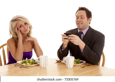 A man texting during his date and the woman is not very happy.