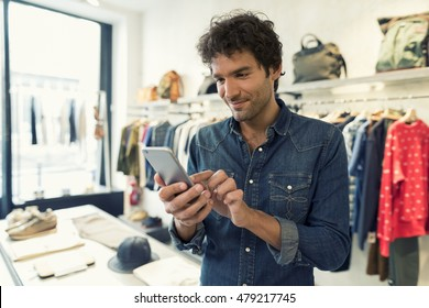 Man texting on cellphone in clothing store