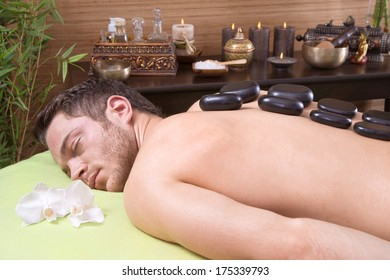 Man at thai spa - making a treatment with hot stone.