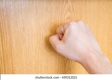 Man (the visitor) is knocking on closed wooden door.