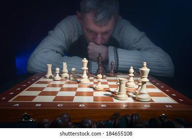 Man thinking behind chessboard. Landscape view