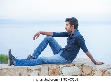 Man thinking looking to blue sky while sitting on a concrete bridge above the sea taking deep breath enjoying freedom at sunset sea on background. Melancholic thoughtful person, peace mind concept.