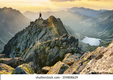 Man thinking and looking to the cloudy sky and calm summer sunset in mountains
