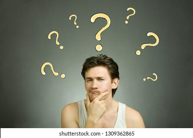 Man thinks and question marks overhead. Stock photo.