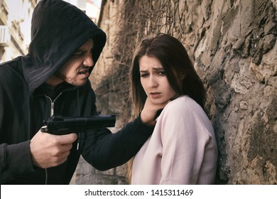 Man threatening woman with gun outdoors. Criminal offence
