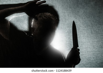 a man is threateningly holding a knife in his hand