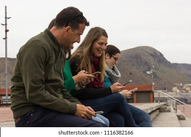 Man and three young women sitting on grandstands using cellphones on cold cloudy day in Las Palmas city, Spain. Group of friends looking at smart phones. New generation mobile device overuse problem