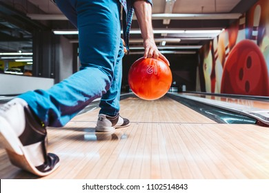 Man throwing ball in bowling alley. View from behind