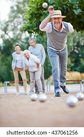 Man throwing ball while playing boule outside in a city
