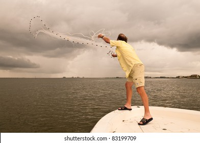 A man throwing a cast net off a bow of a boat