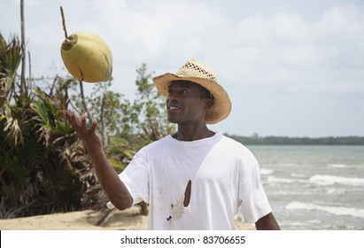 A man throwing and catching a coconut while standing by the sea