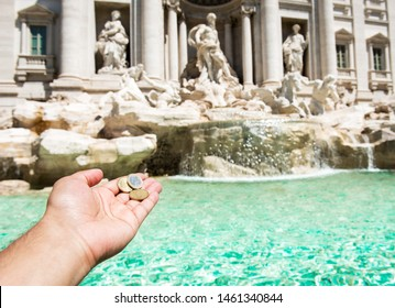 Man is throwing coin at Trevi Fountain for good luck. A man hand keeping coin. Trevi Fountain, Rome, Italy.