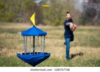 Man throwing flying disk playing disk golf trying to hit disk golf basket