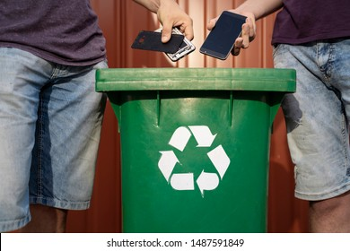 Man throwing phones into recycle bin / obsolete technology, e waste