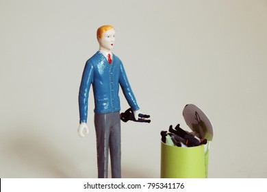 Man throws another tiny man in a trash can. Concept of ditching or trashing a friend, coworker, or bad boss. Stress in dysfunctional relationships. Conflict among people. Men in garbage can.