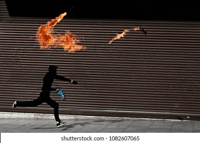 A man throws a petrol bomb  at riot police during clashes with protesters during a 24 hour general strike against the government's austerity politics in Athens, Greece, 2 Decemeber 2015.