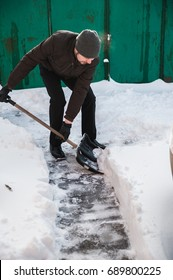 The man throws the shovel snow. The man clears the yard of snow