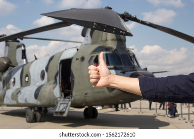 Man with thumb up in front of military helicopter