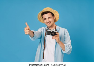 Man thumb and hat on his head blue background camera