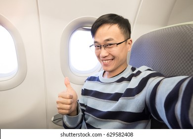 man thumb up and smile happily in the airplane