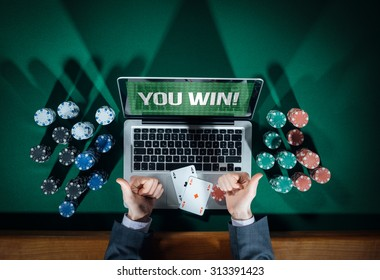 Man thumbs up playing online poker with laptop on a green table with chips all around, top view