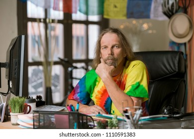 Man in tie dye shirt at his desk