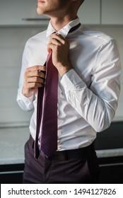 man in a tie, the groom tightens his tie, man puts on a purple tie, purple tie, wedding day, groom's morning