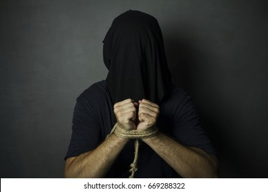 Man with tied hands and black bag on his head