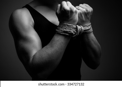 Man with tied hands in low key. Black and white