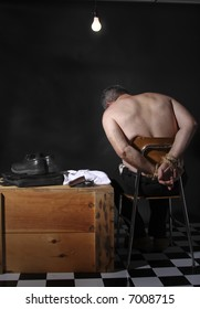 Man tied up on a chair with a overhead light shining down on him in a hostage or kidnapping situation.