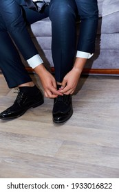 A man ties up his shoelaces on his black shoes in the room. Blue suit and leather shoes. Wedding day, groom.