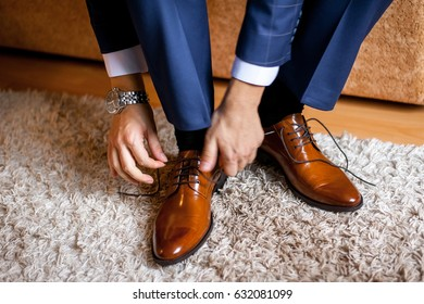 A man ties up his shoelaces on his brown shoes in the room. Blue suit and patent leather shoes.