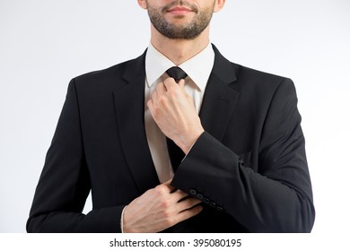 Man ties a necktie knot in a studio against white background