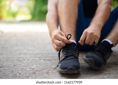 Man ties running shoes, getting ready for jogging