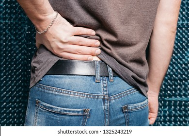 man in tight jeans. sports ass close-up. street style clothing: spring skinny jeans and a gray t-shirt. men's health: The pain caused by hemorrhoid