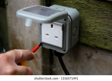 Man tightening external socket box with an electrical screwdriver outdoor outside