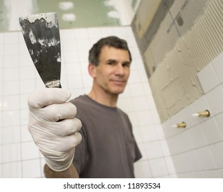 Man tiling the bathroom. Focused close up of hand holding putty knife or trowel. Man and background are out-of-focus.