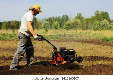 a man tilling ground with motor-cultivator
