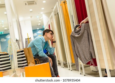Man tired of shopping in clothes shop