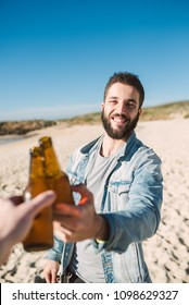 Man toasting with a beer on the beach