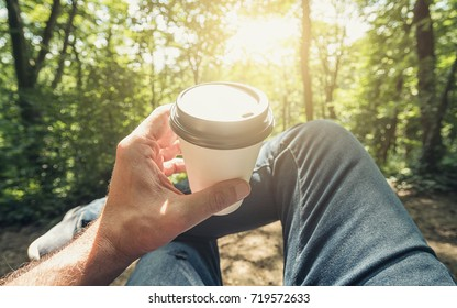 Man toasting coffee take away go cup against explosive sunlight in the forest. Point of view shot