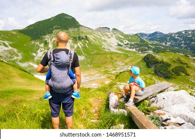 Man with toddler in a carrier and boy sitting on a wooden bench looking at hills on the Alp mountains on circa July 2019 in Ausseerland, Austria.