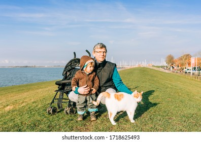 Man with toddler and cat on dyke – Hindeloopen, Netherlands, Europe